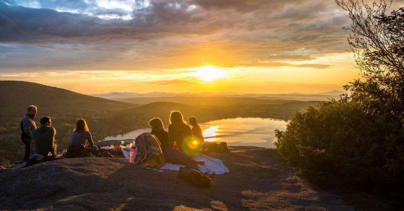Group o fowk sittin unner a sunset